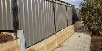 40m Retaining Wall with Galvanized H/C Channels & Timber Sleepers 200x75mm; Colorbond 1.8m High Woodland Grey Sheets & Black Frame Trimline Profile& Gate, in Kilmore, June 2019